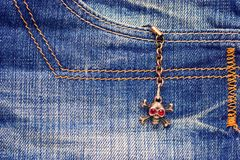 Skull brooch on torn jeans . Stock Images