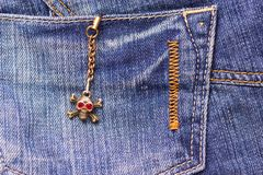 Skull brooch on torn jeans . Stock Image