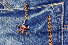 Skull brooch on torn jeans . Royalty Free Stock Image