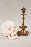 The skull and candle. On a canvas background Stock Photo