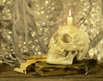 Skull with candle on book. Human skull with burning candle on old book Royalty Free Stock Photo