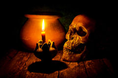 Skull and candle with candlestick on wooden background, still li stock photo