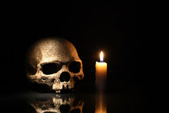 Skull And Candle. Death concept. One human skull near lighting candle on dark background royalty free stock photo
