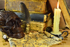 Skull with candle and map. Vintage still life with old books, scary skull, burning candle and shabby map Royalty Free Stock Photo