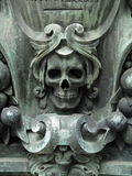Skull in the cemetery. Beautiful death head in bronze patinated by time and elements. Photographed outside on an abandoned grave. Pere Lachaise Cemetery, Paris Royalty Free Stock Image