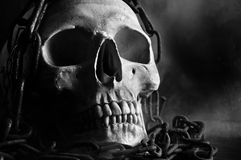 Skull with chain. Human skull with chain and smoke in black and white Royalty Free Stock Image