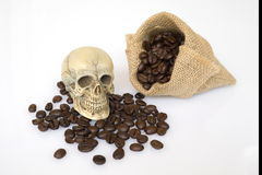 Skull on the coffee. Small skull on the plate near the cup of coffee bean Royalty Free Stock Image