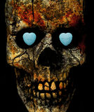 Skull with conversation candy hearts. Conversation candy hearts tucked inside the eye sockets of a textured skull with the words kiss me and I'm yours written on royalty free stock photos