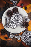 Skull cookies with liquorice flowers for Halloween Stock Images