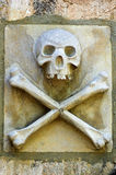 Skull & Crossbones. Skull and crossbones carving on a cemetery wall royalty free stock images