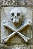 Skull & Crossbones. Skull and crossbones carving on a cemetery wall royalty free stock photography