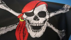 Skull and Crossbones Flag - Jolly Roger. The skull and crossbones is a representation of a skull with two thigh bones crossed below it as an emblem of piracy or stock footage