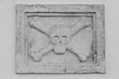 Skull and Crossbones stone sculpture. A stone bas-relief sculpture of a skull and crossbones Stock Photos
