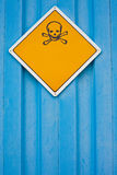 Skull and crossbones warning sign. On blue background white with lots of copyspace for your message royalty free stock photo