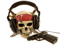 Skull in ear-phones with a lying pistol Royalty Free Stock Photo