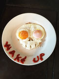 Skull Eggs and Wake Up. Fried eggs in the shape of a creepy, scary skull. Words Wake Up printed in sriracha sauce Royalty Free Stock Photos