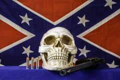 Skull and Flag. Human skull with 357 magnum revolver and three bullets on blue with confederate flag background and house fly on barrel royalty free stock image