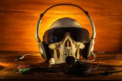 Skull in glasses and with headphones on an old wooden background. A human skull lit by candles on a wooden floor, the concept of H. Skull in glasses and with royalty free stock image