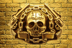 Skull, golden guns and chain on a background of golden brick wal Royalty Free Stock Photo