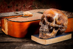 Skull and guitar,book on old wood, Stock Photography