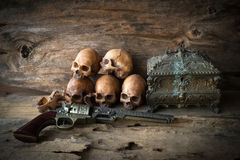 Skull and gun on wood background Royalty Free Stock Image