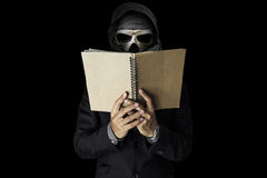 A skull guy in black suit reading notebook, on black dark environment background Stock Photo