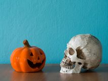 The skull and Halloween pumpkin hat on the wooden table. the background is blue and copy space for text Royalty Free Stock Photos