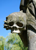 Skull with hand. (part of a stone sculpture royalty free stock image