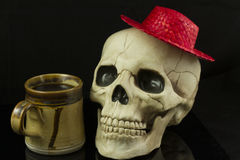 Skull and hat. Skull wearing a red straw hat and having coffee Royalty Free Stock Image