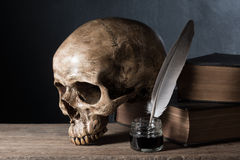 Skull with inkwell. Still life photography : skull with inkwell and old book on art dark background Royalty Free Stock Photo