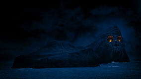 Skull Island With Eyes Of Fire. Mysterious rocky island with skull face in the cliffs and fires burning in the eyes stock video footage