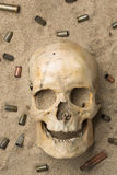 Skull lying in the sand, scattered rifle  Royalty Free Stock Image