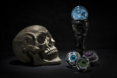 Skull and magic crystal balls with spooky eyes looking Stock Photos