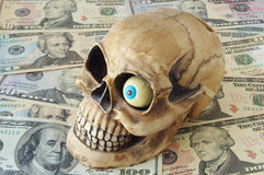 Skull on money. Skull with blue eye lying on scattered dollars Royalty Free Stock Photography