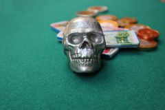 Skull with money on green table stock photography