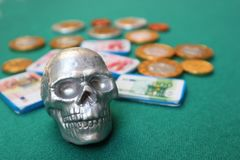 Skull with money on green table. Small decorative silver human skull with money on green table royalty free stock image
