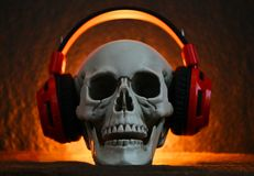 Skull music with headphone / Human skull listening to music earphone decorated at halloween party stock photos
