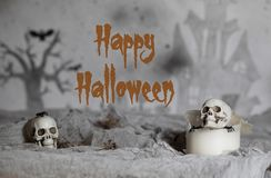 Skull on an old used thick candle. Scary Halloween background. Closeup royalty free stock photo