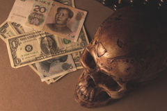 Skull on old wood with banknote yuan and dollar in still life Stock Photos
