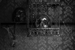 Skull in Ornate Cage Hanging in Candlelit Room Royalty Free Stock Images