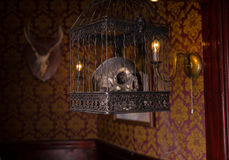 Skull in Ornate Cage Hanging in Candlelit Room Stock Photography