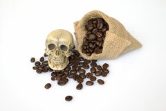 Skull on the plate. Small skull on the plate near the bag of coffee bean Stock Photo