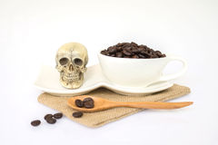 Skull on the plate. Small skull on the plate near the cup of coffee bean Stock Images