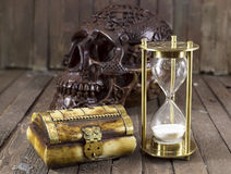Skull with sand clock and box. Still life with creepy skull, sand clock and box on wooden background royalty free stock images