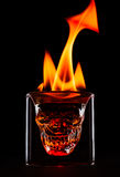 Skull shape glass with flames on the top. Single object on black background Stock Photography
