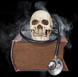 Skull and stethoscope on old  book Stock Photography