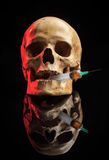 Skull and syringe of yellowish liquid. concept Royalty Free Stock Photos