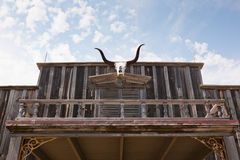 Bull Horns on Western Building. The skull of a Texas longhorn cow is hung above an entrance way of an old western wooden building Stock Photo