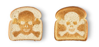 Skull toast. Burnt toast with image of skull and crossbones. Isolated on white royalty free stock image