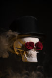 Skull in tophat with red roses in eye sockets Stock Image